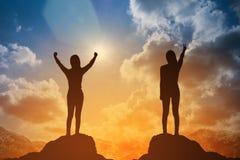 Schattenbild der gewinnenden Erfolgsfrau bei dem Sonnenuntergang oder Sonnenaufgang, die oben ihre Hand in der Feier stehen und a lizenzfreie stockfotos