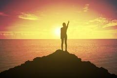 Schattenbild der gewinnenden Erfolgsfrau bei dem Sonnenuntergang oder Sonnenaufgang, die oben ihre Hand in kämpfendem Konzept ste Stockbild