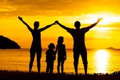Schattenbild der glücklichen Familie das, die auf dem Strand spielt Stockbilder