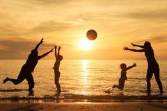 Schattenbild der glücklichen Familie das, die auf dem Strand am sunse spielt Stockfoto