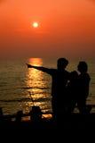 Schattenbild der glücklichen Familie das, die auf dem Strand am sunse spielt lizenzfreie stockfotografie