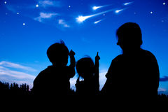 Schattenbild der glücklichen Familie Himmel Kometen sitzend und betrachtend Lizenzfreie Stockfotos