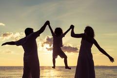 Schattenbild der glücklichen Familie das, die auf dem Strand am sunse spielt Lizenzfreie Stockfotos