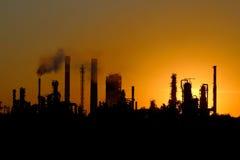 Schattenbild der großen Erdölraffineriefabrik während des Sonnenuntergangs Stockfotos