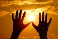 Schattenbild der Hände gegen den orange Sonnenuntergang. Lizenzfreies Stockfoto