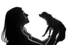 Schattenbild der hübschen Frau stehend mit smal Hund in ihren Händen Sie hob Haustier über dem Kopf und den Blicken auf ihm mit a Lizenzfreies Stockbild