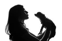 Schattenbild der hübschen Frau stehend mit smal Hund in ihren Händen Sie hob Haustier über dem Kopf und den Blicken auf ihm mit a Lizenzfreie Stockfotografie