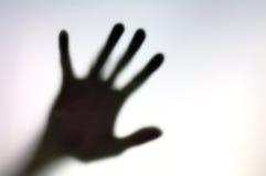 Schattenbild der Hand auf einer weißen Oberfläche Stockbild
