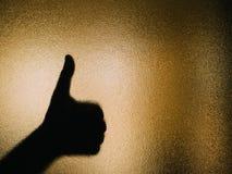 Schattenbild der Hand Daumen oben auf einem Glas herstellend lizenzfreie stockbilder