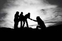 Schattenbild der Handreichung zwischen Bergsteiger zwei lizenzfreie stockfotografie
