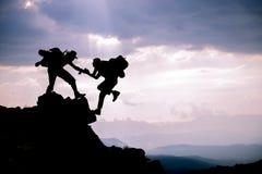 Schattenbild der Handreichung zwischen Bergsteiger zwei Abenteuerliche Leute; Wanderer, die auf Berg klettern Hilfe, Risiko, Unte lizenzfreies stockfoto