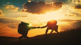 Schattenbild der Handreichung zwischen Bergsteiger zwei zwei Wanderer auf den Berg, ein Mann hilft einem Mann, ein blo?es zu klet stock footage