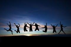 Die Jugendlichen springend in Sonnenuntergang Lizenzfreie Stockfotografie