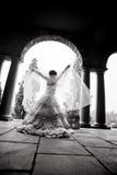 Schattenbild der jungen Frau Brautkleid im Torbogen tragend lizenzfreie stockfotografie