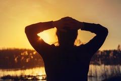 Schattenbild der jungen Frau den Sonnenuntergang betrachtend Lizenzfreies Stockfoto