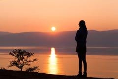 Schattenbild der jungen Frau gegen Sonnenuntergang über See Lizenzfreie Stockfotos