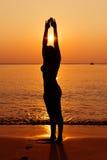 Schattenbild der jungen Frau im Meer auf Sonnenuntergang Lizenzfreies Stockbild