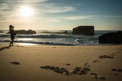 Schattenbild der jungen Frau stehend auf dem szenischen sandigen Strand, der Fotos des schönen Meerblicks von Atlantik mit Wellen Lizenzfreies Stockbild