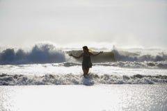 Schattenbild der jungen glücklichen Asiatin entspannte sich, wilde Meereswellen auf tropischem Strand des Sonnenuntergangs betrac Stockbild