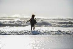 Schattenbild der jungen glücklichen Asiatin entspannte sich, wilde Meereswellen auf tropischem Strand des Sonnenuntergangs betrac Lizenzfreies Stockfoto