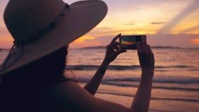 Schattenbild der jungen touristischen Frau im Hut, der Foto mit Mobiltelefon während des Sonnenuntergangs im Ozeanstrand macht Stockbild