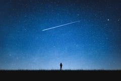 Schattenbild der Mädchenstellung auf Berg und nächtlichem Himmel mit Sternschnuppe alleinkonzept stockfotos