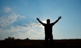 Schattenbild der Mannanbetung mit den Händen angehoben zum Himmel in der Natur Stockfotografie