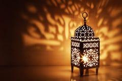 Schattenbild der marokkanischen dekorativen Laterne mit brennender glühender Kerze Dekorative Schatten Festliche Grußkarte stockfotografie