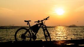Schattenbild der Mountainbike in Meer mit Sonnenuntergang Lizenzfreies Stockbild