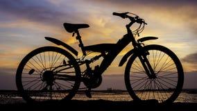 Schattenbild der Mountainbike mit Sonnenunterganghimmel Lizenzfreie Stockfotos