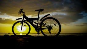 Schattenbild der Mountainbike mit Sonnenunterganghimmel Stockbilder