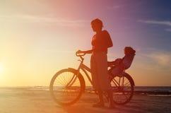 Schattenbild der Mutter und des Babys, die bei Sonnenuntergang radfahren Stockbilder