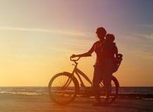 Schattenbild der Mutter und des Babys, die bei Sonnenuntergang radfahren Stockfotos