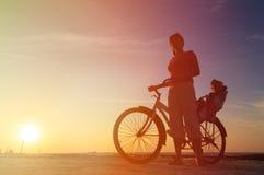 Schattenbild der Mutter und des Babys, die bei Sonnenuntergang radfahren Lizenzfreies Stockbild