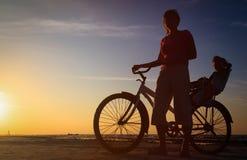 Schattenbild der Mutter und des Babys, die bei Sonnenuntergang radfahren Lizenzfreie Stockfotografie