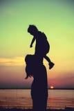 Schattenbild der Mutter und des Kindes, welche die Ansicht am Flussufer genießen C Lizenzfreies Stockfoto