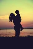 Schattenbild der Mutter und des Kindes, welche die Ansicht am Flussufer genießen C Stockbilder