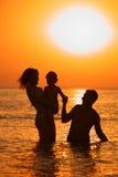 Schattenbild der Muttergesellschaft mit Kind im Meer auf Sonnenuntergang Stockfotos