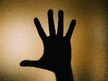 Schattenbild der offenen Hand auf einem Glas stockfotos