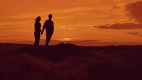Schattenbild der Paare, die auf Strand an den Sonnenuntergangholdinghänden gehen glücklicher Mann und Mädchen auf Küste in den Li stock footage