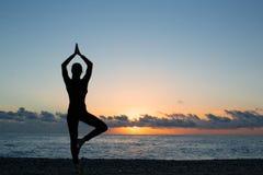 Schattenbild der Person Yoga auf dem Strand bei Sonnenaufgang tuend lizenzfreie stockfotos