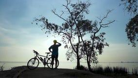 Schattenbild der Radfahrerfrau gehend mit Fahrrad an der Küste, Übung ausdehnend stock video
