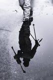 Schattenbild der Reflexion eines Skifahrers, der zum Skiaufzug vorangeht Stockfotografie