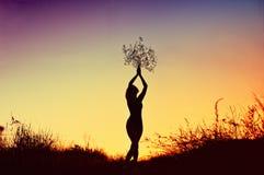 Schattenbild der schönen jungen Frau, die einen Blumenstrauß über ihrem Kopf am Sonnenunterganggrasland hält Stockbild