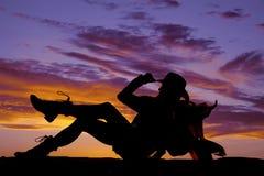 Schattenbild der sitzenden Hand des Frauencowgirls auf Hutsattel sollte an Stockbild