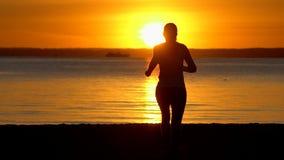 Schattenbild der sportlichen Frau des Läufers, die auf Seeozeanstrand bei Sonnenuntergang läuft Weiblicher Rüttler, der in der Na stock footage