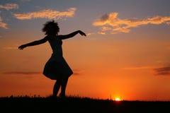 Schattenbild der Tanzenfrau auf Sonnenuntergang Lizenzfreies Stockfoto