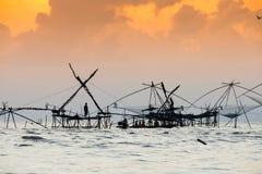 Schattenbild der traditionellen Fangtechnik unter Verwendung eines quadratischen BambusKeschers mit Sonnenaufganghimmelhintergrun Lizenzfreie Stockfotografie