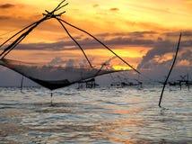 Schattenbild der traditionellen Fangtechnik unter Verwendung eines quadratischen BambusKeschers mit Sonnenaufganghimmelhintergrun Lizenzfreie Stockbilder