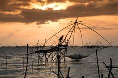 Schattenbild der traditionellen Fangtechnik unter Verwendung eines quadratischen BambusKeschers mit Sonnenaufganghimmelhintergrun Lizenzfreie Stockfotos